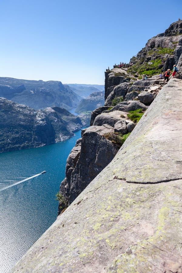 Взгляд на Lysefjord и крутой скале Preikestolen на горе Kjerag Пассажирское судно плавает от деревни Lysebotn Поход людей к p стоковое фото