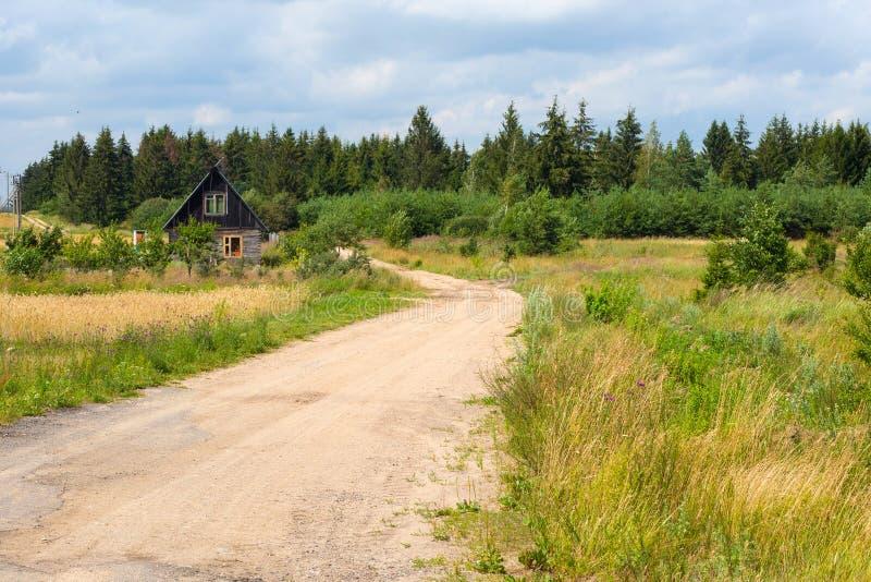 Взгляд небольшой дороги около деревянного дома стоковое фото
