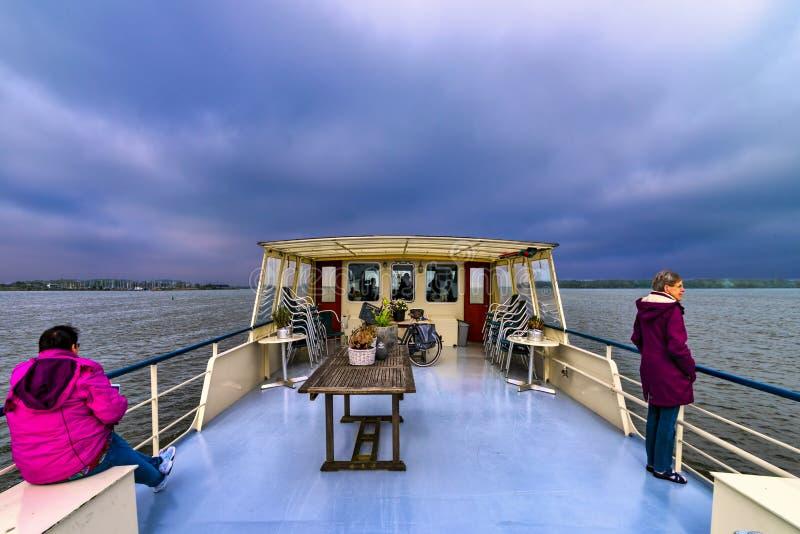 Взгляд Нидерланд Ijselmeer 06-05-2018 от палубы старого плавания рыбацкой лодки через озеро в зимнем времени, с серым-b стоковые изображения rf