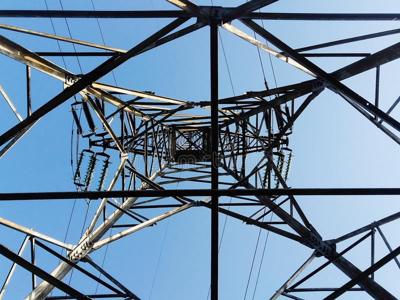 Взгляд низкого угла высокого штендера электричества изнутри против голубого неба стоковая фотография rf