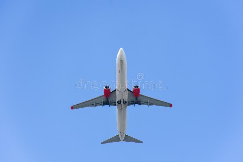 Взгляд низкого угла летания самолета под голубым небом стоковое фото rf