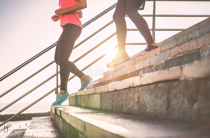 Взгляд ног бегунов имея встречу разминки на лестницах города на открытом воздухе - близкий вверх людей бежать на заходе солнца стоковые изображения rf