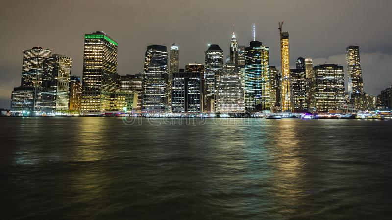 Взгляд ночи более низкого Манхэттена Свет небоскребов отражен в воде стоковая фотография rf