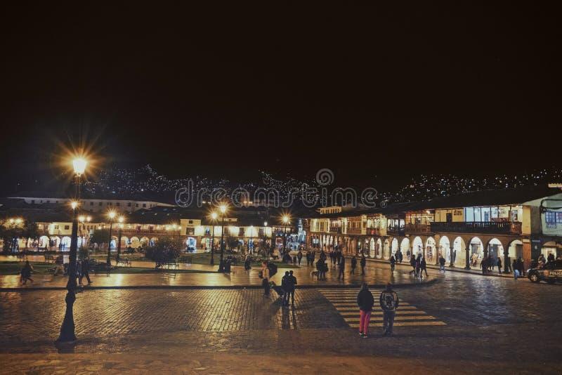 Взгляд ночи главной площади зоны Cusco, Перу Много туристов принимают прогулки или ходят по магазинам там стоковые фотографии rf