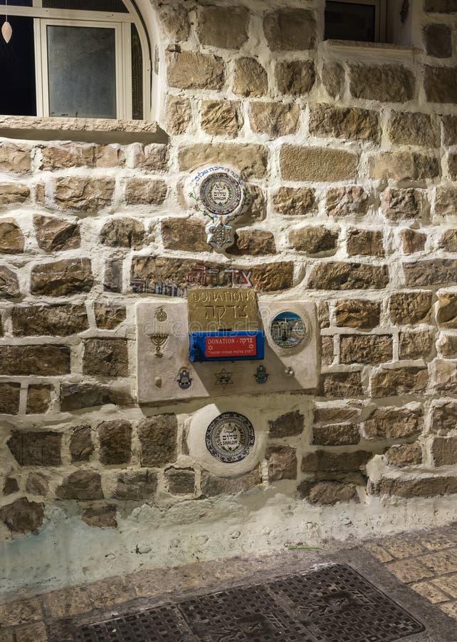 Взгляд ночи декоративных орнаментов и место для пожертвований прикрепленное к стене дома на тихой улице в старом городе  стоковое изображение