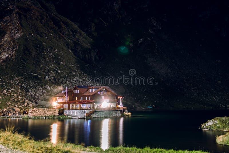Взгляд ночи на доме, гостинице на береге озера горы, Lac Balea, концепции туризма и каникул, перемещении и активном образе жизни, стоковое фото rf