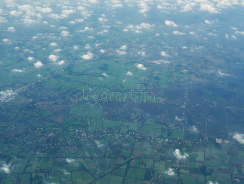 Взгляд облаков и полей от самолета стоковые фотографии rf