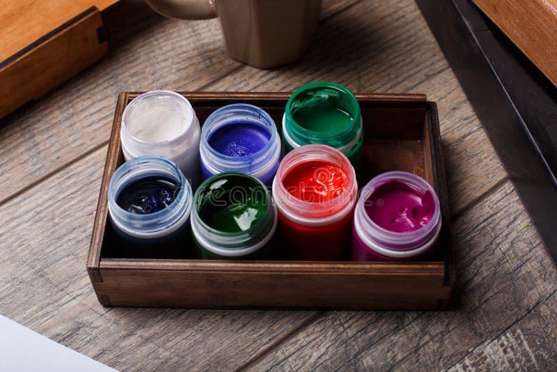 Взгляд объектов для рисовать Щетки, краски в коробке для материалов на деревянном партере белизна пятна краски маски принципиальн стоковые фотографии rf
