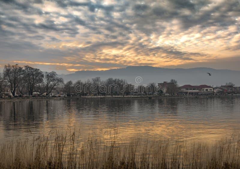 Взгляд озера Pamvotis на заходе солнца с отражениями Город Янины, стоковое изображение rf