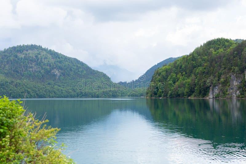 Взгляд открытки озера Alpsee окруженный горами Альп, Баварией, Германией Лето весны Голубая чистая вода Никто стоковые изображения