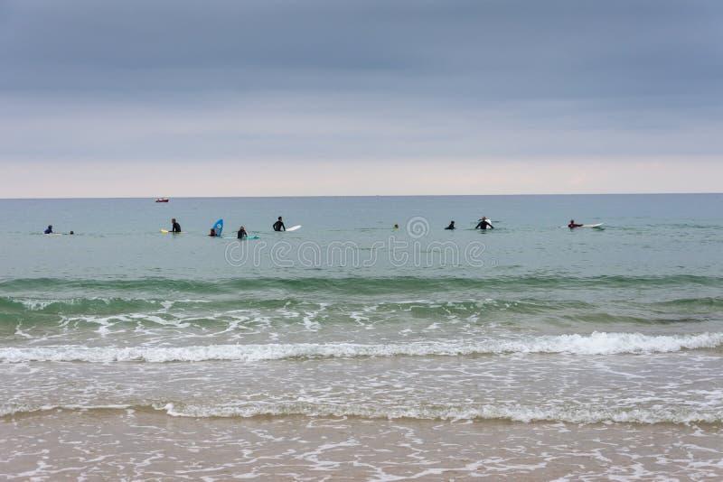 Взгляд от пляжа группы в составе серферы ждать волны, пасмурное после полудня стоковые изображения rf