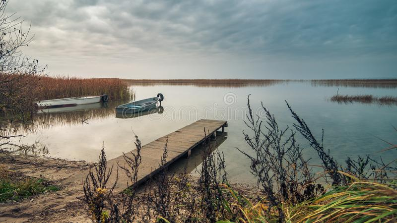 взгляд от побережья озера к красивому ландшафту воды со шлюпкой, деревянной пристанью и прибрежными тростниками в свете осеннего стоковые фото
