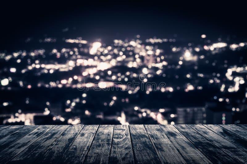 Взгляд от пустого деревянного пола планки над городком вечером стоковые фото
