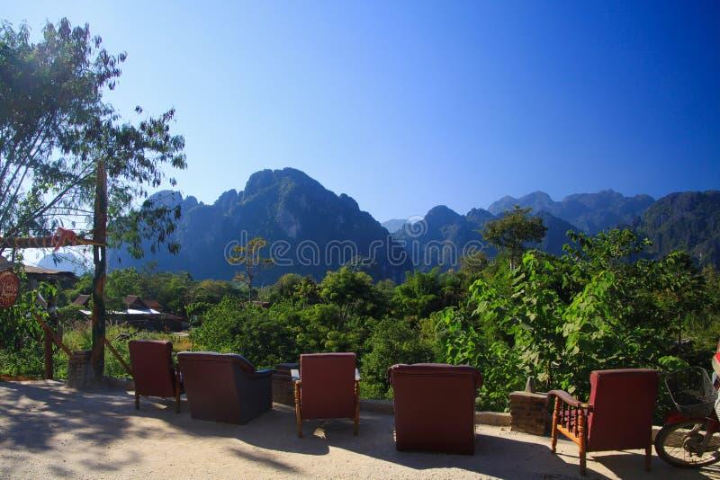Взгляд от ресторана на строке кресел и холмов karst вдоль реки Xong песни Nam стоковое изображение