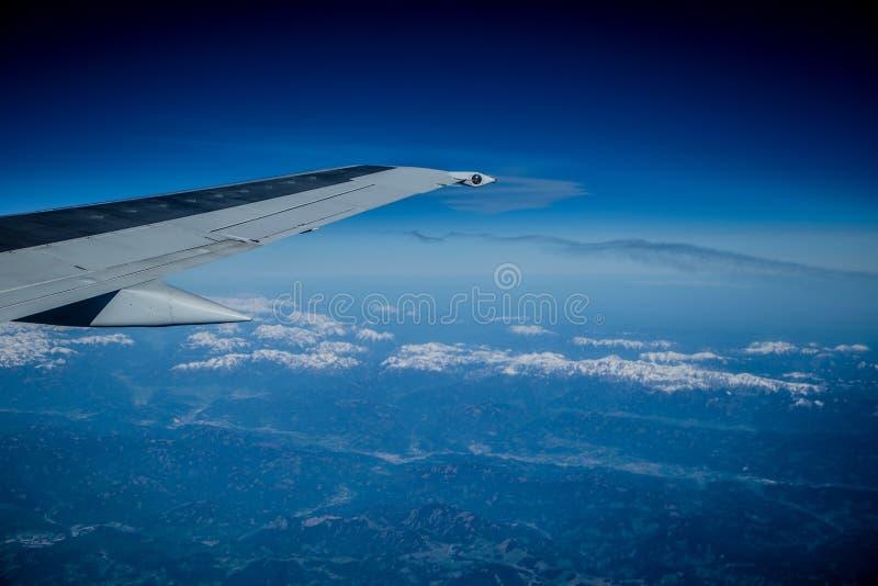 Взгляд от самолета на горах и облаках стоковое фото