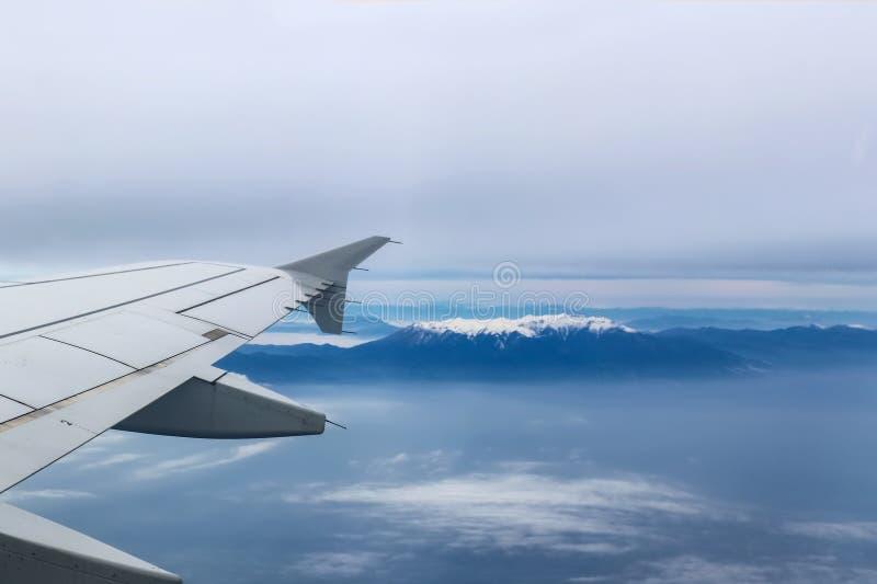 Взгляд от самолета с летанием крыла над Mt Olympus Грецией с покрытым снег пиком показывая через густой туман стоковое фото