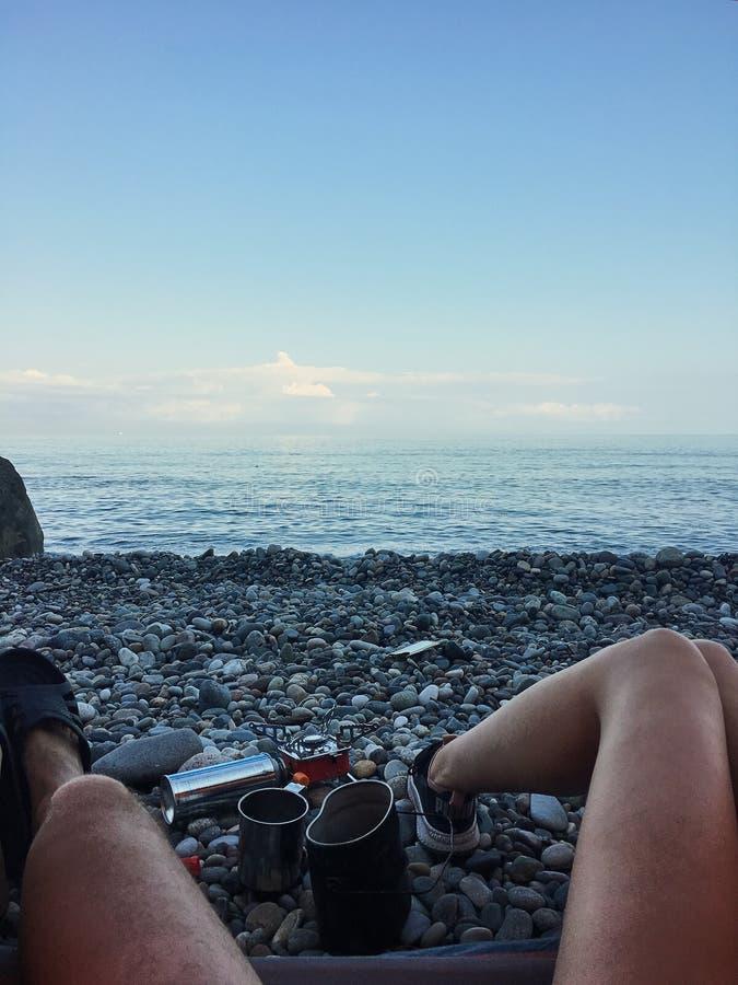 Взгляд от шатра на пляже, человеческих ногах лежа в туристском шатре с взглядом моря, Pebble Beach, газовой горелки, завтрака в п стоковое изображение rf