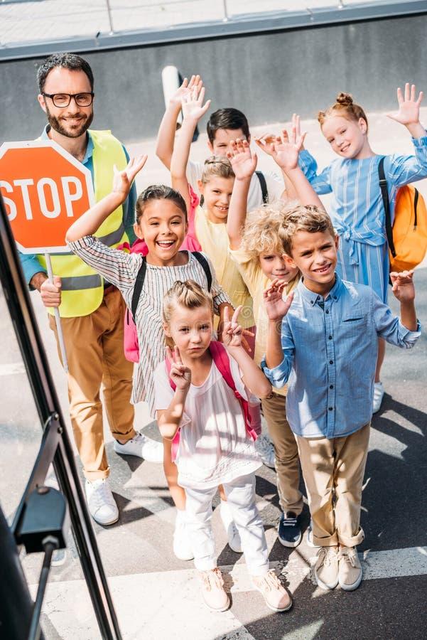 взгляд от школьного автобуса на группе в составе ученые с предохранителем движения смотря камеру стоковые изображения rf