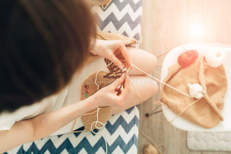Взгляд от abov eof молодая женщина вязать теплый бежевый свитер на кровати Милая собака дворняжкы кроме Домашняя, независимая, ha стоковые изображения