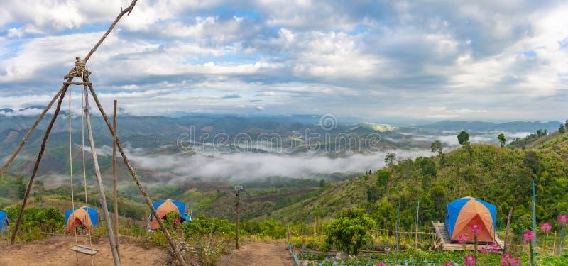 Взгляд панорамы долины горы с шатром туристов на переднем плане и облачным небом с туманом стоковые фото