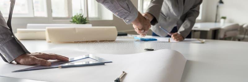 Взгляд панорамы рукопожатия 2 деловых партнеров стоковое фото