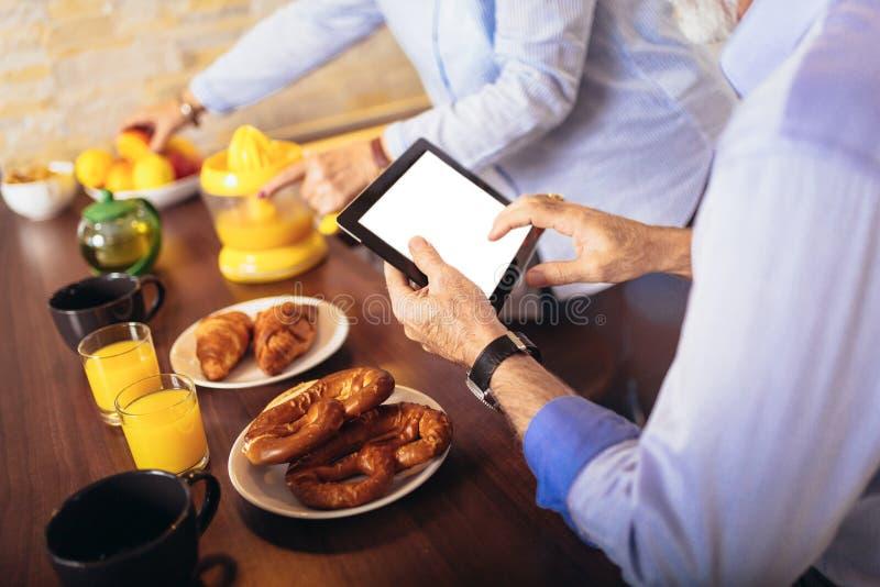 Взгляд пар занятый на цифровом планшете пока имеющ очень вкусную кухню завтрака дома стоковое фото rf