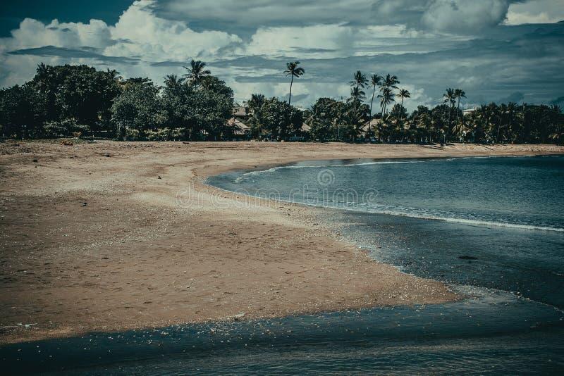 Взгляд пляжа песка Kuta Перемещение Бали Исследуйте красивый ландшафт Индонезии Концепция туризма Азии Известный тропический роск стоковые изображения