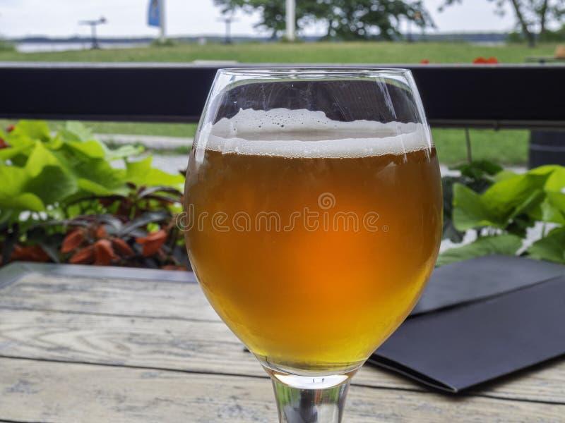 Взгляд полного стекла пива от стороны на деревянном столе, outdoors с красивым видом в сериях дневного света пузырей, пиво как ра стоковые фото