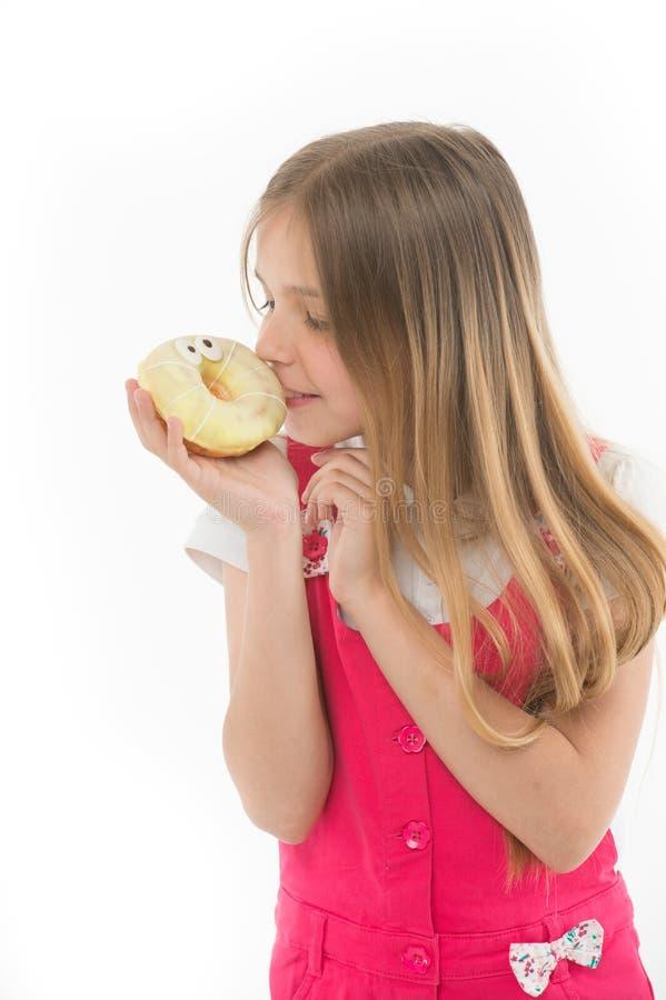 Взгляд ребенка на донуте изолированном на белизне Маленькая девочка с застекленным донутом кольца Ребенк с высококалорийной вредн стоковые фото
