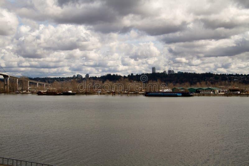 Взгляд реки с баржами состыковал на далекой стороне стоковая фотография rf