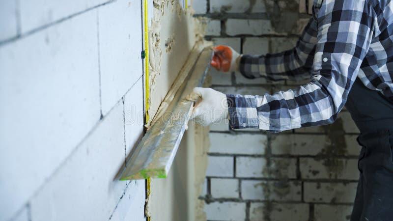 Взгляд рук построителя в перчатках используя правителя конструкции для штукатурить стоковые фотографии rf