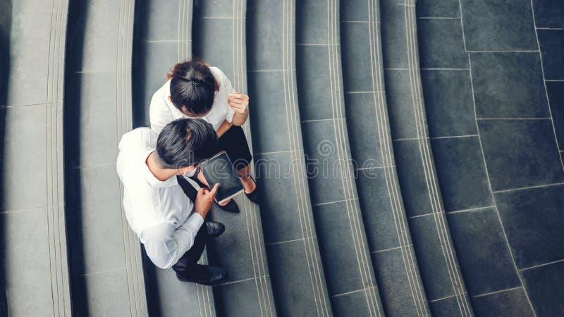 Взгляд сверху азиатских бизнесменов встречая и используя цифровое tabl стоковое фото