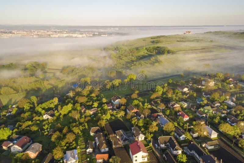 Взгляд сверху белого тумана на крышах дома в деревне среди зеленых деревьев под ярким голубым небом Панорама ландшафта весны тума стоковое фото