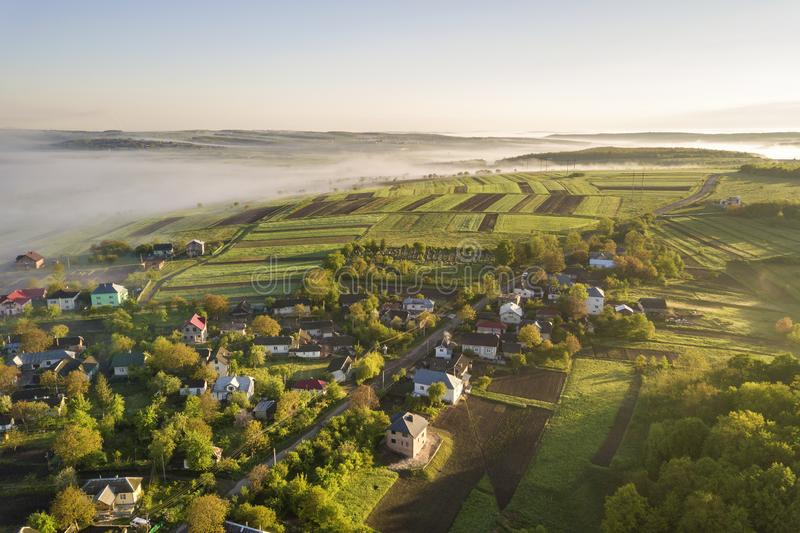 Взгляд сверху белого тумана на крышах дома в деревне среди зеленых деревьев под ярким голубым небом Панорама ландшафта весны тума стоковое изображение