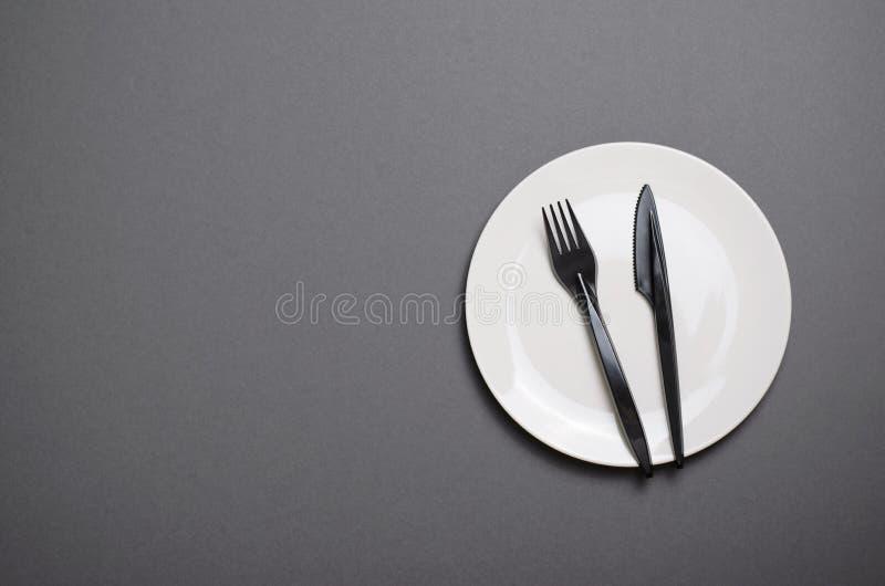 Взгляд сверху белой плиты с черным столовым прибором на серой предпосылке, концепции обедающего стоковое изображение rf