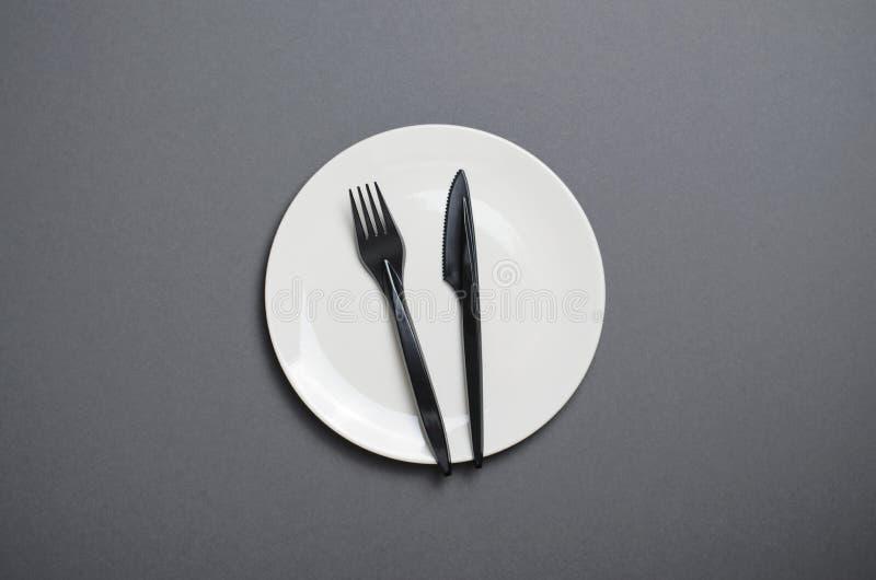 Взгляд сверху белой плиты с черным столовым прибором на серой предпосылке, концепции обедающего стоковое фото