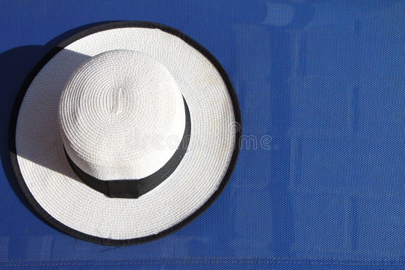 Взгляд сверху белой шляпы пляжа с черной лентой лежа на голубом шезлонге стоковое фото