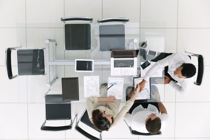 Взгляд сверху бизнесмен и коммерсантка рукопожатия на встрече в офисе стоковое фото