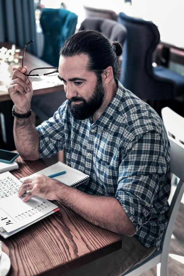Взгляд сверху бородатого человека чувствуя занятый пока изучающ иностранный язык стоковые изображения rf