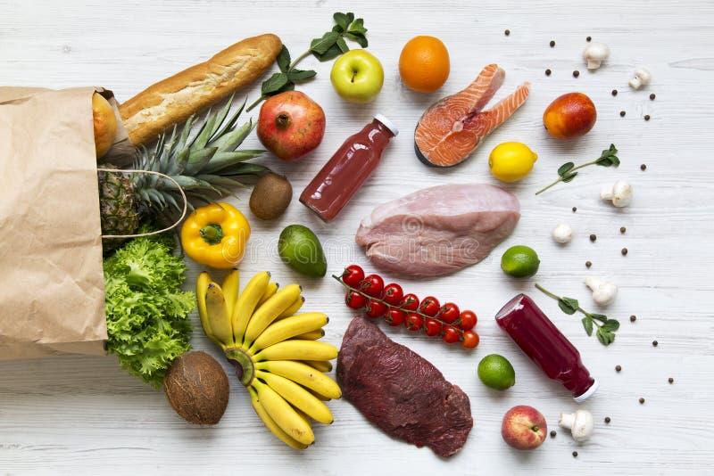 Взгляд сверху, бумажная сумка различных здоровых продуктов над белой деревянной предпосылкой стоковое изображение