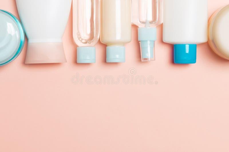 Взгляд сверху бутылок косметик на розовой предпосылке Концепция заботы кожи с космосом для вашего дизайна стоковые изображения