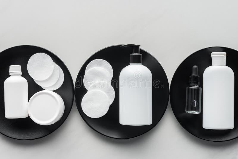 взгляд сверху бутылок сливк и косметических пусковых площадок на 3 черных плитах стоковое фото
