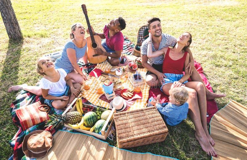 Взгляд сверху высокого угла счастливых семей имея потеху с детьми на партии барбекю nic pic - Multiracial концепции любов стоковое изображение rf