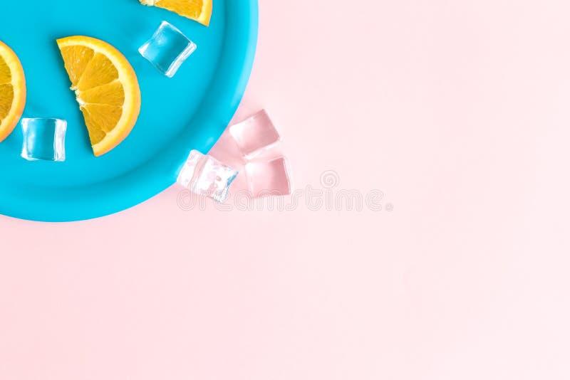 Взгляд сверху голубой плиты с кубами льда и оранжевыми кусками плода изолированными на пастельной розе Концепция освежения лета стоковая фотография rf