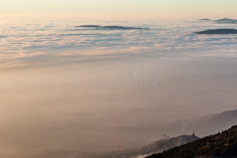 Взгляд сверху городка Умбрии Assisi, Италии в середине тумана, с красивыми, теплыми цветами захода солнца стоковые изображения rf