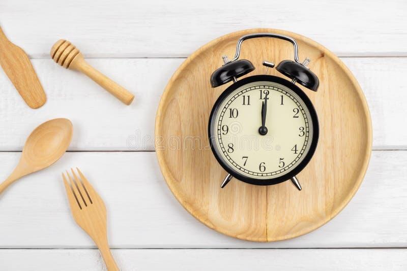 Взгляд сверху деревянного блюда и утварей еды с часами стоковые изображения