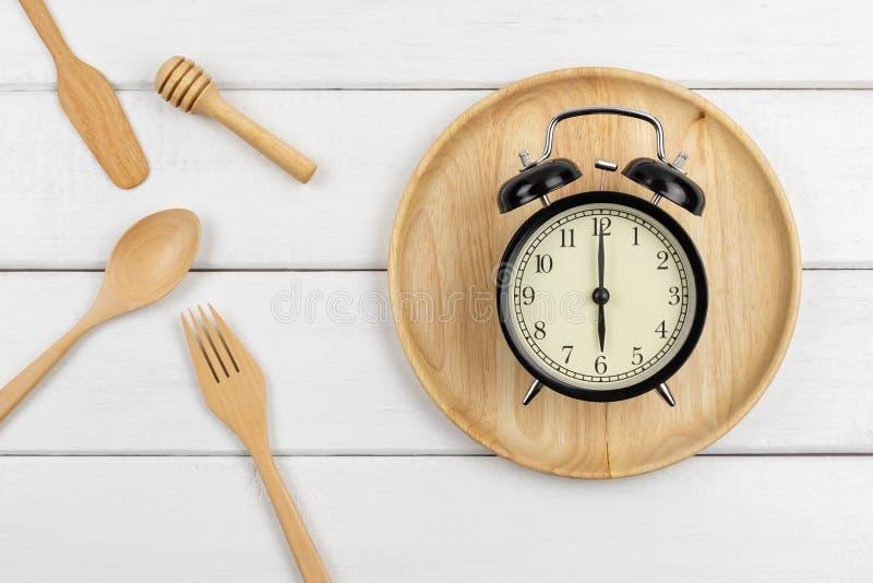 Взгляд сверху деревянного блюда и утварей еды с часами стоковое изображение