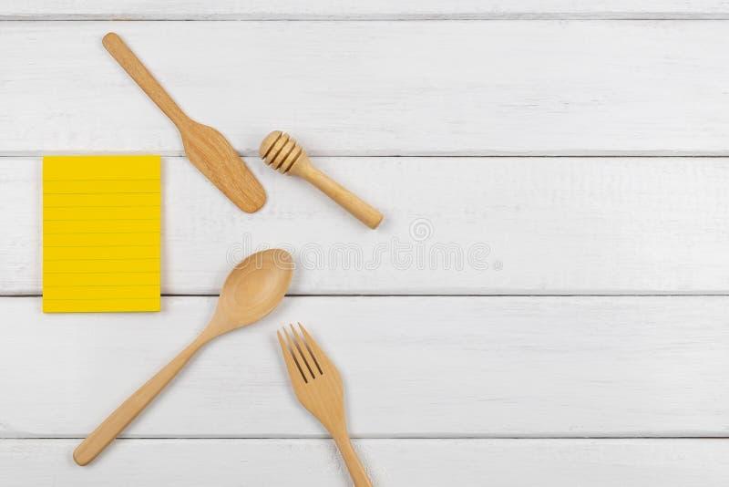 Взгляд сверху желтого пустого липкого примечания с едой утварей стоковое фото