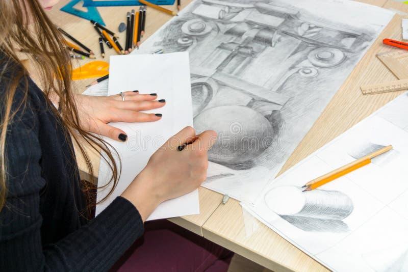 Взгляд сверху женского дизайнера архитектора рисует эскизы в карандаше на белой бумаге Черно-белый чертеж архитектурноакустическо стоковые фотографии rf