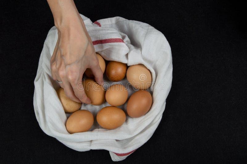 Взгляд сверху женской руки комплектуя свежее яйцо от белой ткани на столешнице стоковые изображения